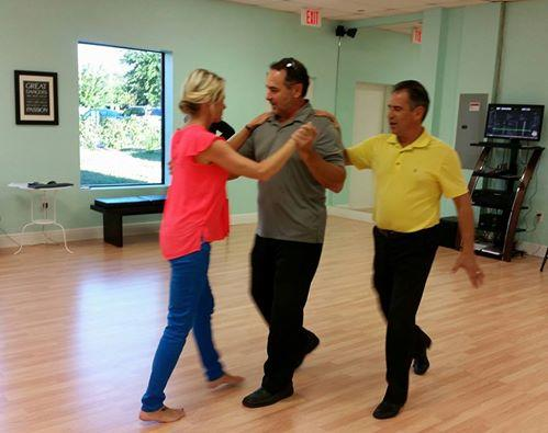 Couple rehearsing their wedding dance with their instructor.